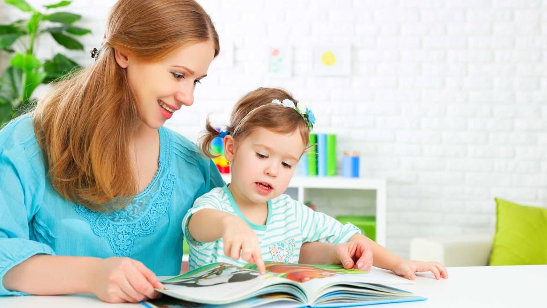 Мама с дочкой листают книгу